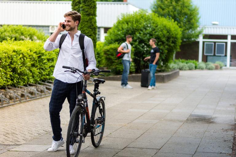 Lutz Heiny mit einem Fahrrad und am telefonieren vor dem Euregium Nordhorn