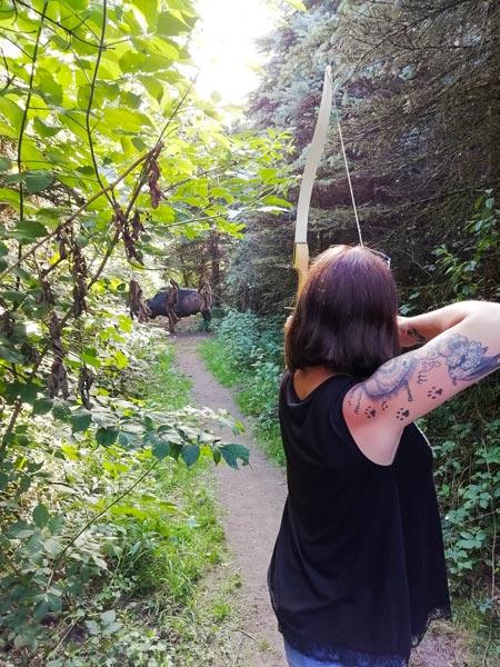 Frau schießt mit Bogen auf Attrappe